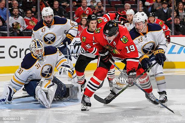 Jonathan Toews of the Chicago Blackhawks and Sam Reinhart of the Buffalo Sabres battle for the puck in front of goalie Chad Johnson in the second...