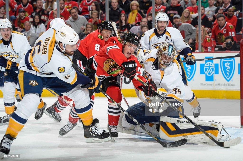 Jonathan Toews of the Chicago Blackhawks and Shea Weber of the Nashville Predators reach for the puck next to Predators goalie Pekka Rinne as Marian...