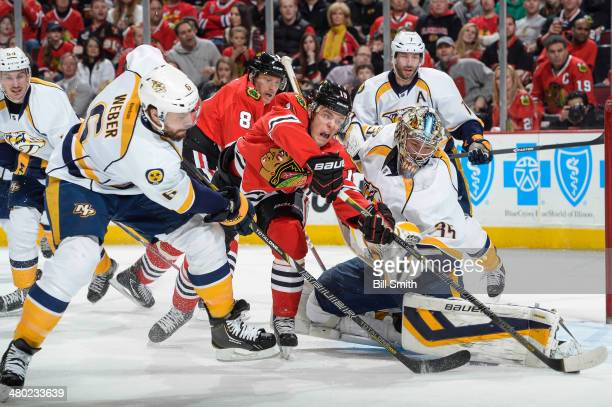 Jonathan Toews of the Chicago Blackhawks and Shea Weber of the Nashville Predators reach for the puck next to Predators goalie Pekka Rinne as Marian...