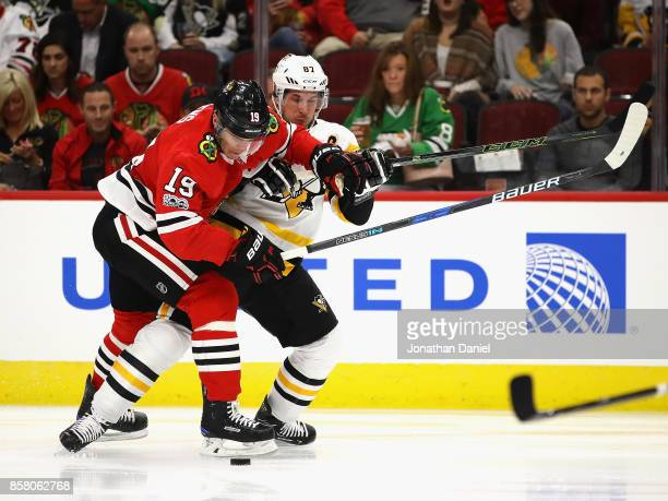 Jonathan Toews of the Chicago Blackhawks and Sidney Crosby of the Pittsburgh Penguins battle for the puck during the season opening game at the...
