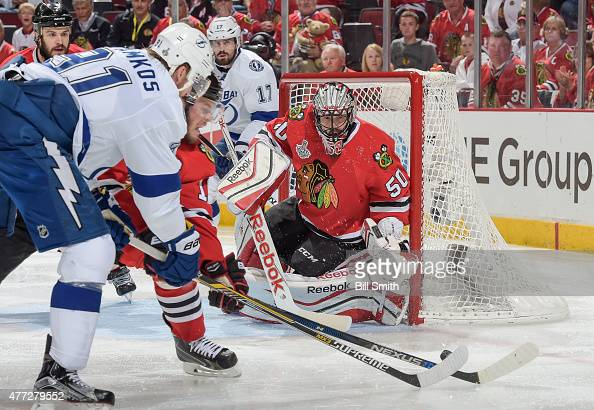 Jonathan Toews of the Chicago Blackhawks and Steven Stamkos of the Tampa Bay Lightning chase the puck past goalie Corey Crawford during Game Six of...