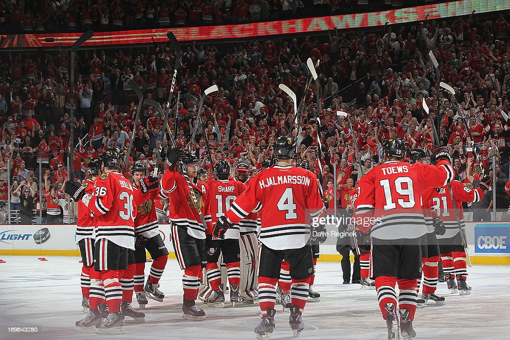 Jonathan Toews #19 of the Chicago Blackhawks and teammates salute the fans after winning 2-1 in overtime after Game Seven of the Western Conference Semifinals during the 2013 NHL Stanley Cup Playoffs at United Center on May 29, 2013 in Chicago, Illinois.