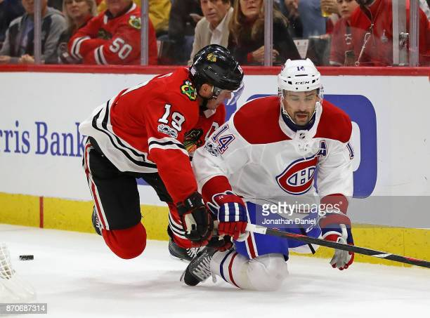 Jonathan Toews of the Chicago Blackhawks and Tomas Plekanec of the Montreal Canadiens hit the ice going for the puck at the United Center on November...