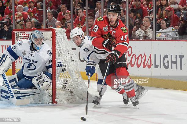 Jonathan Toews of the Chicago Blackhawks and Tyler Johnson of the Tampa Bay Lightning chase the puck around goalie Andrei Vasilevskiy during Game...