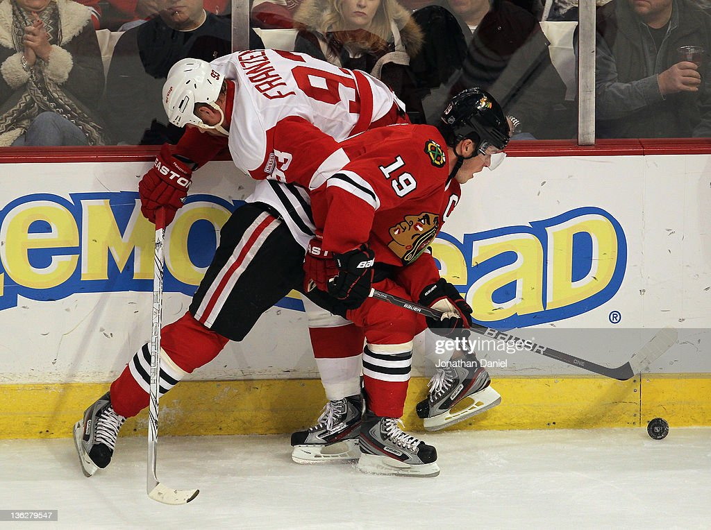 <a gi-track='captionPersonalityLinkClicked' href=/galleries/search?phrase=Jonathan+Toews&family=editorial&specificpeople=537799 ng-click='$event.stopPropagation()'>Jonathan Toews</a> #19 of the Chicago Blackhawks battles for the puck along the boards with <a gi-track='captionPersonalityLinkClicked' href=/galleries/search?phrase=Johan+Franzen&family=editorial&specificpeople=624356 ng-click='$event.stopPropagation()'>Johan Franzen</a> #93 of the Detroit Red Wings at the United Center on December 30, 2011 in Chicago, Illinois.