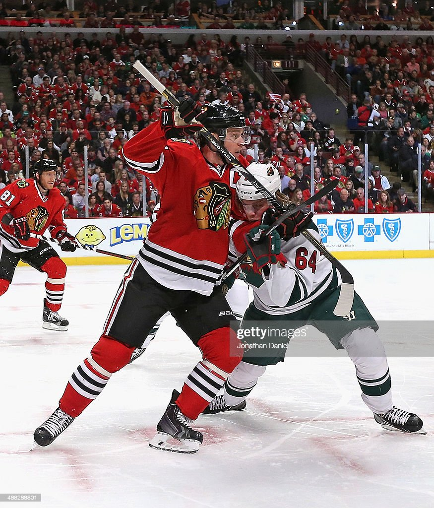 Jonathan Toews #19 of the Chicago Blackhawks battles with Mikael Granlund #64 of the Minnesota Wild during a face-off in Game Two of the Second Round of the 2014 NHL Stanley Cup Playoffs at the United Center on May 4, 2014 in Chicago, Illinois. The Blackhawks defeated the Wild 4-1.