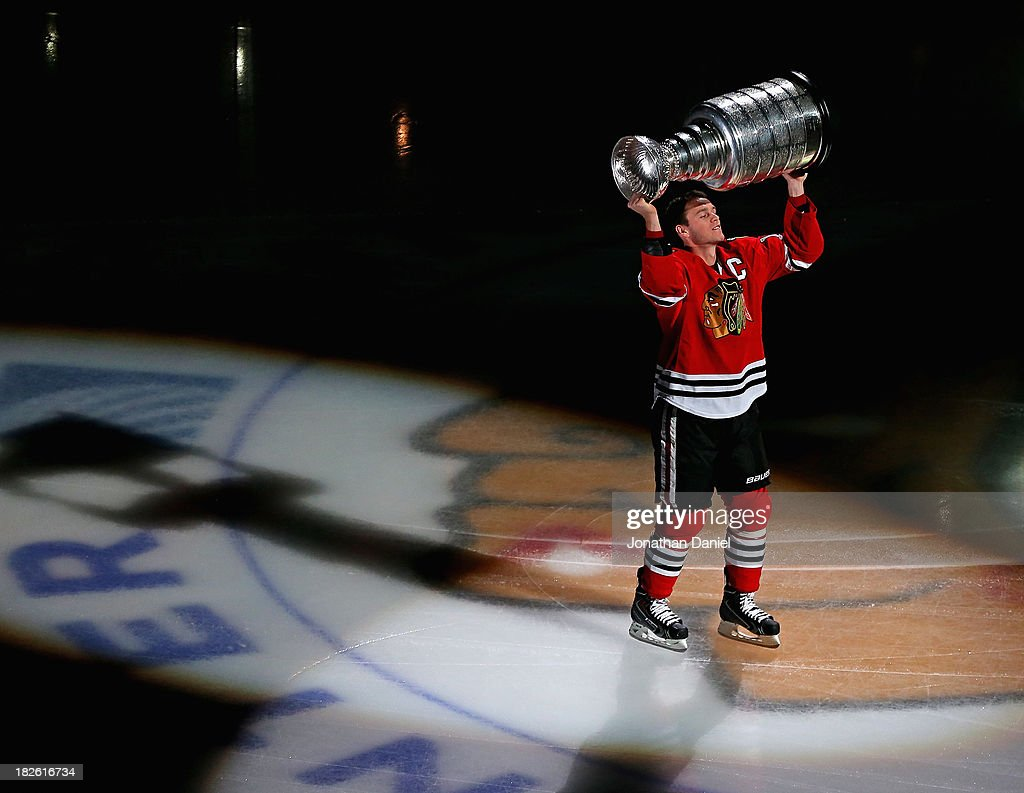 Jonathan Toews #19 of the Chicago Blackhawks carries the Stanley Cup one last time during a ceremony before taking on the Washington Capitals at the United Center on October 1, 2013 in Chicago, Illinois.