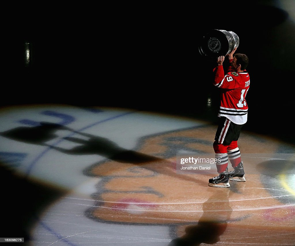 Jonathan Toews #19 of the Chicago Blackhawks carries the Stanley Cup one last time during a ceremony before taking on the Washington Capitals at the United Center on October 1, 2013 in Chicago, Illinois. The Blackhawks defeated the Capitals 5-4.