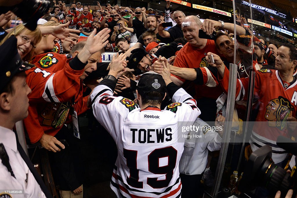 <a gi-track='captionPersonalityLinkClicked' href=/galleries/search?phrase=Jonathan+Toews&family=editorial&specificpeople=537799 ng-click='$event.stopPropagation()'>Jonathan Toews</a> #19 of the Chicago Blackhawks celebrates with fans following their 3-2 win against the Boston Bruins in Game Six of the 2013 NHL Stanley Cup Final at TD Garden on June 24, 2013 in Boston, Massachusetts.