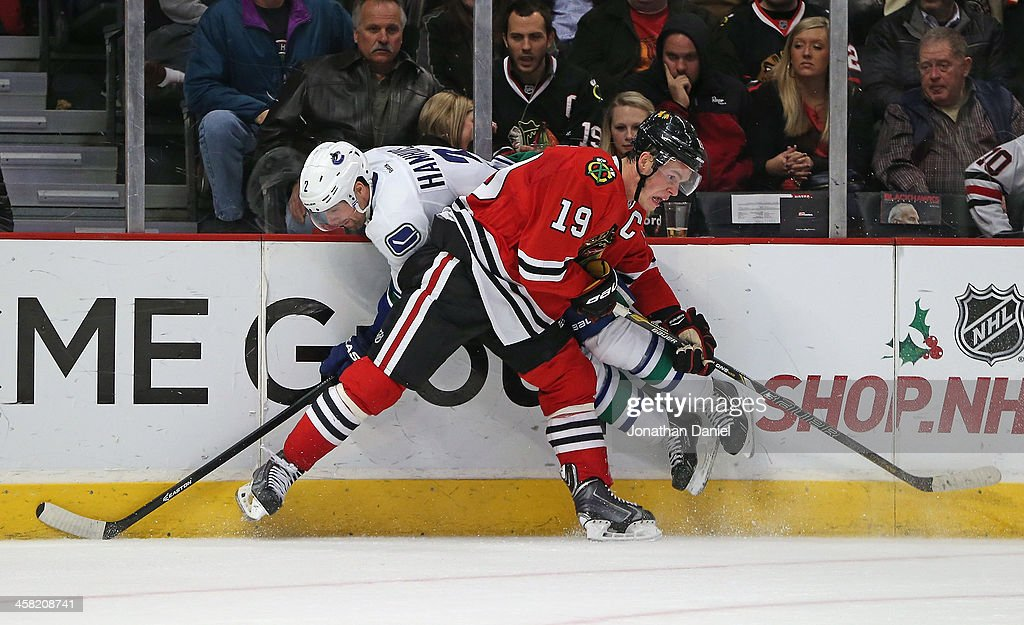 <a gi-track='captionPersonalityLinkClicked' href=/galleries/search?phrase=Jonathan+Toews&family=editorial&specificpeople=537799 ng-click='$event.stopPropagation()'>Jonathan Toews</a> #19 of the Chicago Blackhawks collides with <a gi-track='captionPersonalityLinkClicked' href=/galleries/search?phrase=Dan+Hamhuis&family=editorial&specificpeople=204213 ng-click='$event.stopPropagation()'>Dan Hamhuis</a> #2 of the Vancouver Canucks at the United Center on December 20, 2013 in Chicago, Illinois. The Canucks defeated the Blackhawks 3-2 in a shootout.