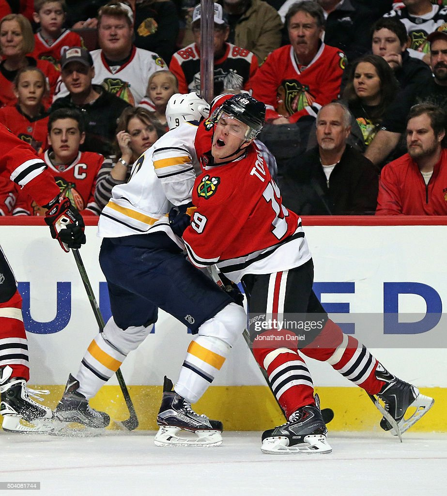 Jonathan Toews #19 of the Chicago Blackhawks collides with Evander Kane #9 of the Buffalo Sabres at the United Center on January 8, 2016 in Chicago, Illinois.