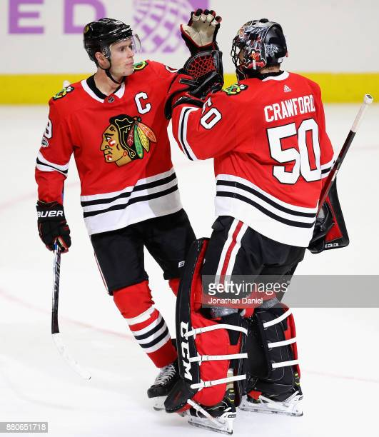 Jonathan Toews of the Chicago Blackhawks congratulates Corey Crawford after a win over the Anaheim Ducks at the United Center on November 27 2017 in...