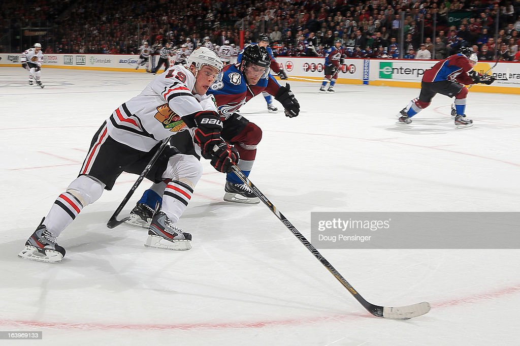 Jonathan Toews #19 of the Chicago Blackhawks controls the puck against Jan Hejda #8 of the Colorado Avalanche at the Pepsi Center on March 18, 2013 in Denver, Colorado.