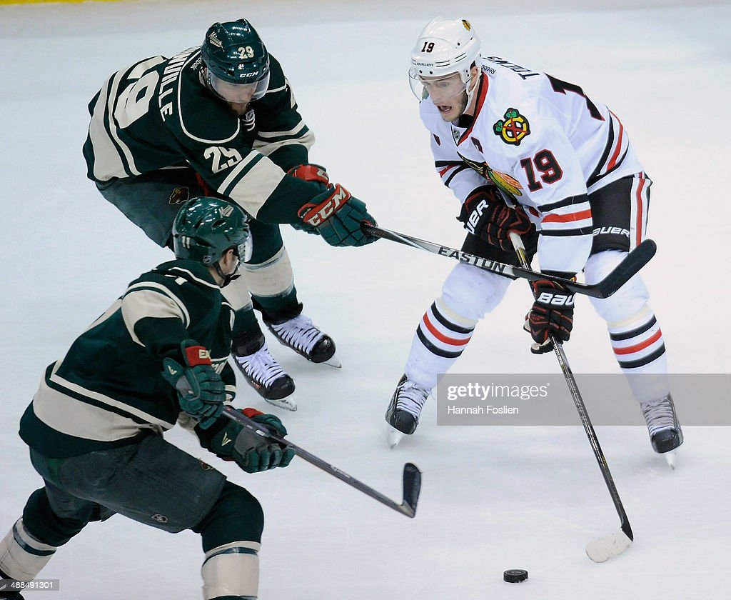 Jonathan Toews #19 of the Chicago Blackhawks controls the puck against Zach Parise #11 and Jason Pominville #29 of the Minnesota Wild during the first period in Game Three of the Second Round of the 2014 NHL Stanley Cup Playoffs on May 6, 2014 at Xcel Energy Center in St Paul, Minnesota.