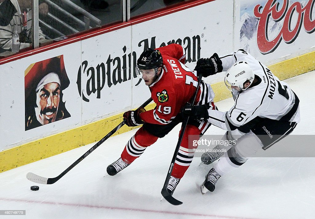 Jonathan Toews #19 of the Chicago Blackhawks controls the puck against Jake Muzzin #6 of the Los Angeles Kings in the first period in Game Two of the Western Conference Final during the 2014 Stanley Cup Playoffs at United Center on May 21, 2014 in Chicago, Illinois.