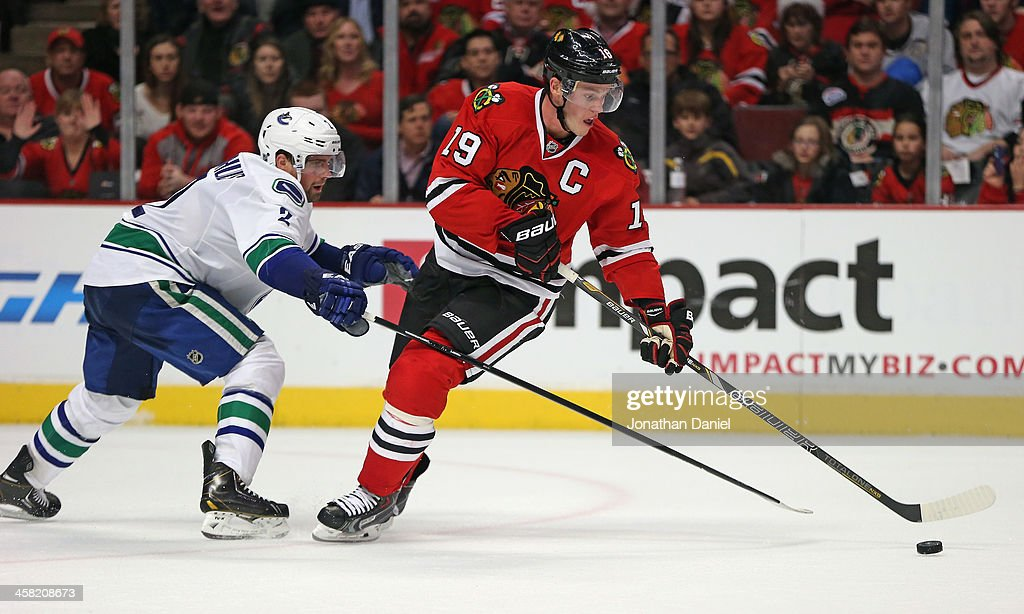<a gi-track='captionPersonalityLinkClicked' href=/galleries/search?phrase=Jonathan+Toews&family=editorial&specificpeople=537799 ng-click='$event.stopPropagation()'>Jonathan Toews</a> #19 of the Chicago Blackhawks controls the puck under pressure from <a gi-track='captionPersonalityLinkClicked' href=/galleries/search?phrase=Dan+Hamhuis&family=editorial&specificpeople=204213 ng-click='$event.stopPropagation()'>Dan Hamhuis</a> #2 of the Vancouver Canucks at the United Center on December 20, 2013 in Chicago, Illinois. The Canucks defeated the Blackhawks 3-2 in a shootout.