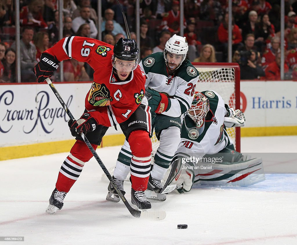Jonathan Toews #19 of the Chicago Blackhawks controls the puck under pressure from Matt Moulson #26 and Ilya Bryzgalov #30 of the Minnesota Wild in Game Two of the Second Round of the 2014 NHL Stanley Cup Playoffs at the United Center on May 4, 2014 in Chicago, Illinois. The Blackhawks defeated the Wild 4-1.