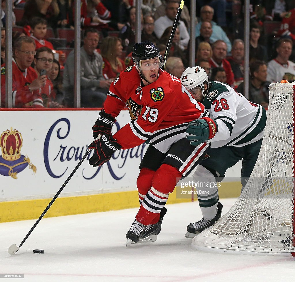 Jonathan Toews #19 of the Chicago Blackhawks controls the puck under pressure from Matt Moulson #26 of the Minnesota Wild in Game Two of the Second Round of the 2014 NHL Stanley Cup Playoffs at the United Center on May 4, 2014 in Chicago, Illinois. The Blackhawks defeated the Wild 4-1.