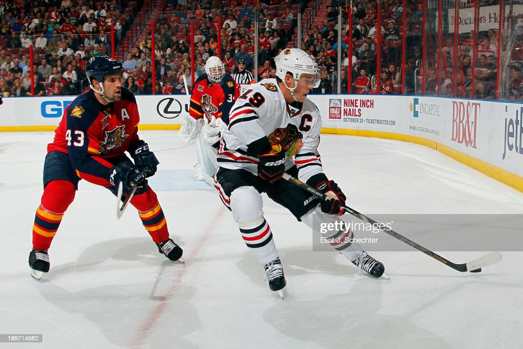 <a gi-track='captionPersonalityLinkClicked' href=/galleries/search?phrase=Jonathan+Toews&family=editorial&specificpeople=537799 ng-click='$event.stopPropagation()'>Jonathan Toews</a> #19 of the Chicago Blackhawks digs the puck out from the boards against Mike Weaver #43 of the Florida Panthers at the BB&T Center on October 22, 2013 in Sunrise, Florida.