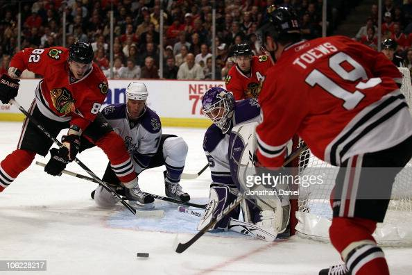 Jonathan Toews of the Chicago Blackhawks fires a shot at Jonathan Bernier and Rob Scuden of the Los Angeles Kings as teammate Tomas Kopecky setsup...