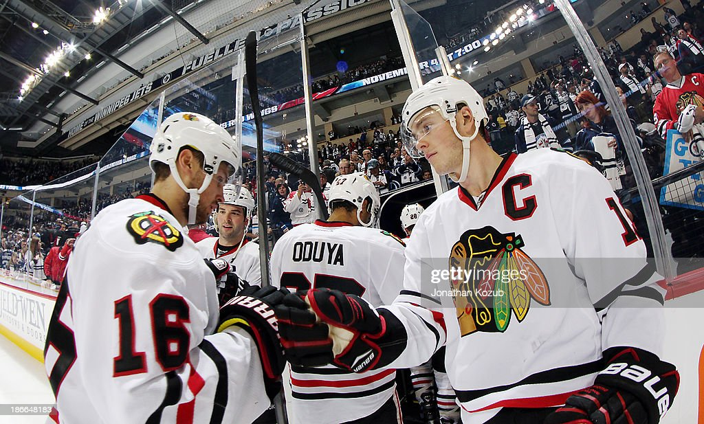 <a gi-track='captionPersonalityLinkClicked' href=/galleries/search?phrase=Jonathan+Toews&family=editorial&specificpeople=537799 ng-click='$event.stopPropagation()'>Jonathan Toews</a> #19 of the Chicago Blackhawks fist bumps teammate Marcus Kruger #16 as he leaves the ice following a 5-1 victory over the Winnipeg Jets at the MTS Centre on November 2, 2013 in Winnipeg, Manitoba, Canada.