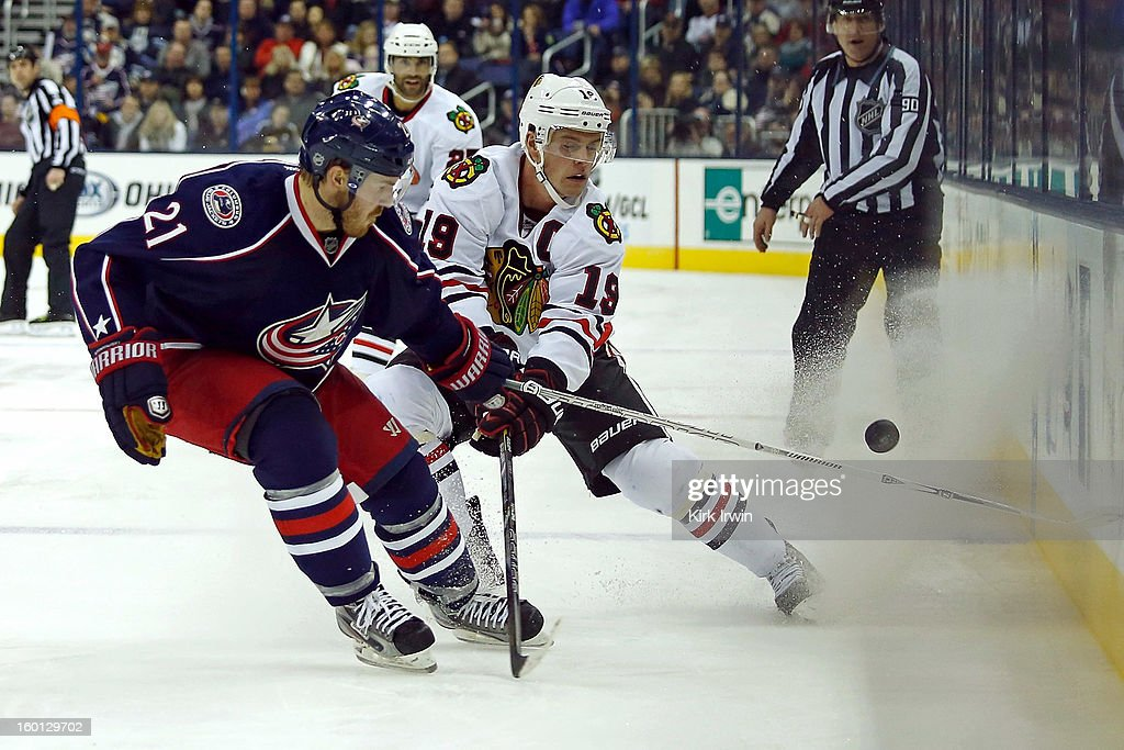 Jonathan Toews #19 of the Chicago Blackhawks flips the puck past James Wisniewski #21 of the Columbus Blue Jackets during the third period on January 26, 2013 at Nationwide Arena in Columbus, Ohio. Chicago defeated Columbus 3-2.