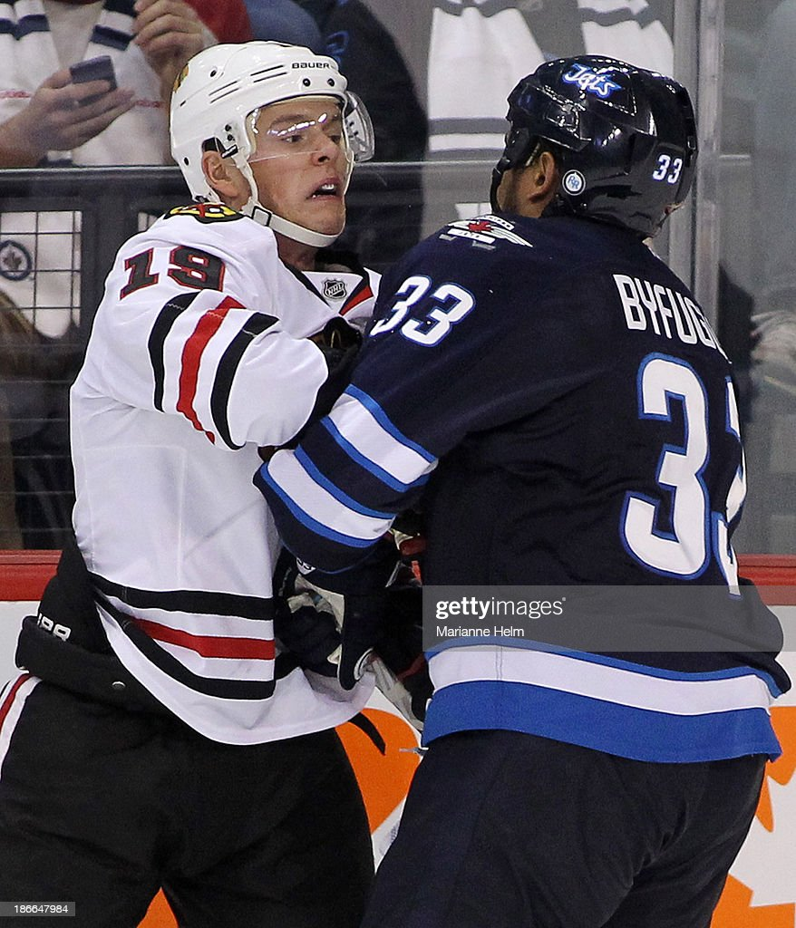 <a gi-track='captionPersonalityLinkClicked' href=/galleries/search?phrase=Jonathan+Toews&family=editorial&specificpeople=537799 ng-click='$event.stopPropagation()'>Jonathan Toews</a> #19 of the Chicago Blackhawks gets roughed up by <a gi-track='captionPersonalityLinkClicked' href=/galleries/search?phrase=Dustin+Byfuglien&family=editorial&specificpeople=672505 ng-click='$event.stopPropagation()'>Dustin Byfuglien</a> #33 of the Winnipeg Jets in third period action in an NHL game at the MTS Centre on November 2, 2013 in Winnipeg, Manitoba, Canada.