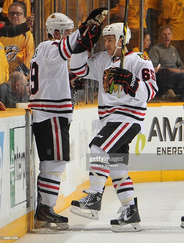 Jonathan Toews #19 of the Chicago Blackhawks high fives teammate Andrew Shaw #65 after defeating the Nashville Predators in the second overtime period of Game One of the Western Conference Quarterfinals during the 2015 NHL Stanley Cup Playoffs at Bridgestone Arena on April 15, 2015 in Nashville, Tennessee.