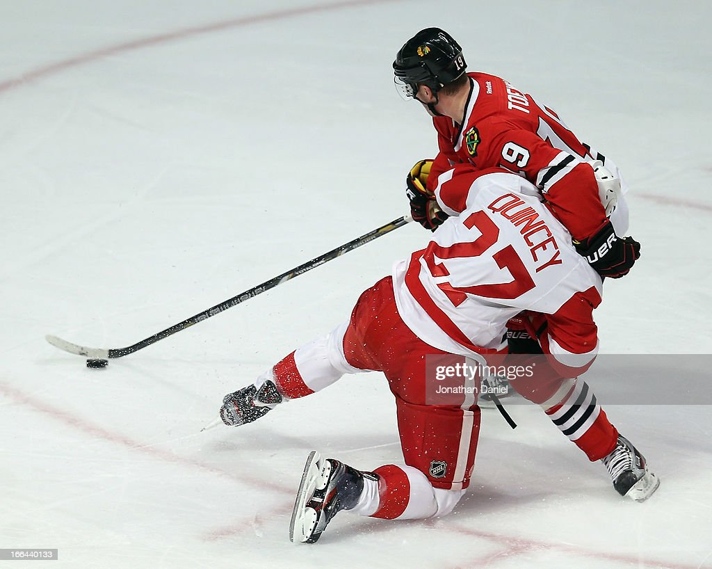 <a gi-track='captionPersonalityLinkClicked' href=/galleries/search?phrase=Jonathan+Toews&family=editorial&specificpeople=537799 ng-click='$event.stopPropagation()'>Jonathan Toews</a> #19 of the Chicago Blackhawks holds off <a gi-track='captionPersonalityLinkClicked' href=/galleries/search?phrase=Kyle+Quincey&family=editorial&specificpeople=2234340 ng-click='$event.stopPropagation()'>Kyle Quincey</a> #27 of the Detroit Red Wings with one arm as he advances the puck at the United Center on April 12, 2013 in Chicago, Illinois.
