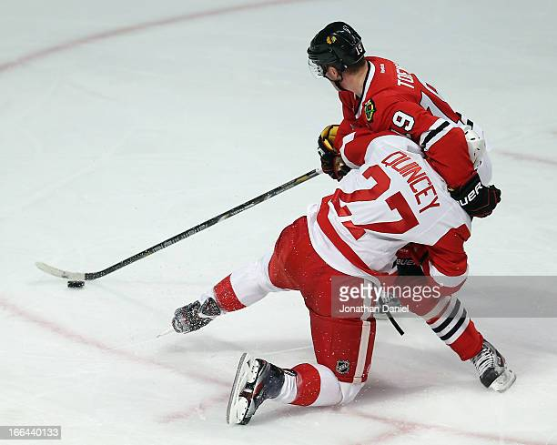 Jonathan Toews of the Chicago Blackhawks holds off Kyle Quincey of the Detroit Red Wings with one arm as he advances the puck at the United Center on...