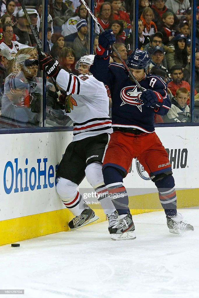 Jonathan Toews #19 of the Chicago Blackhawks is checked by Derek Dorsett #15 of the Columbus Blue Jackets while chasing after a loose puck during the third period on January 26, 2013 at Nationwide Arena in Columbus, Ohio. Chicago defeated Columbus 3-2.