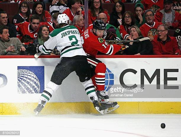 Jonathan Toews of the Chicago Blackhawks is checked into the boards be Jyrki Jokipakka of the Dallas Stars at the United Center on February 11 2016...