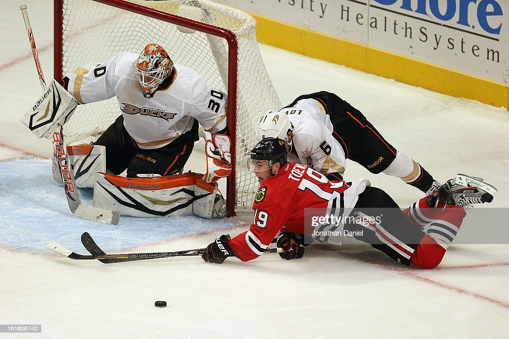 Jonathan Toews #19 of the Chicago Blackhawks is knocked down by Ben Lovejoy #6 of the Anaheim Ducks as he tries to shoot against Viktor Fasth #30 at the United Center on February 12, 2013 in Chicago, Illinois. The Ducks defeated the Blackhawks 3-2 in a shootout.