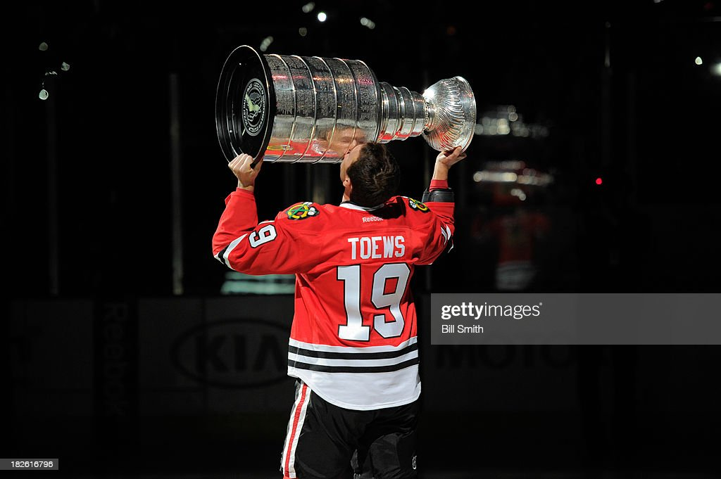 Jonathan Toews #19 of the Chicago Blackhawks kisses the Stanley Cup during the opening ceremony before the home opener against the Washington Capitals on October 1, 2013 at the United Center in Chicago, Illinois.