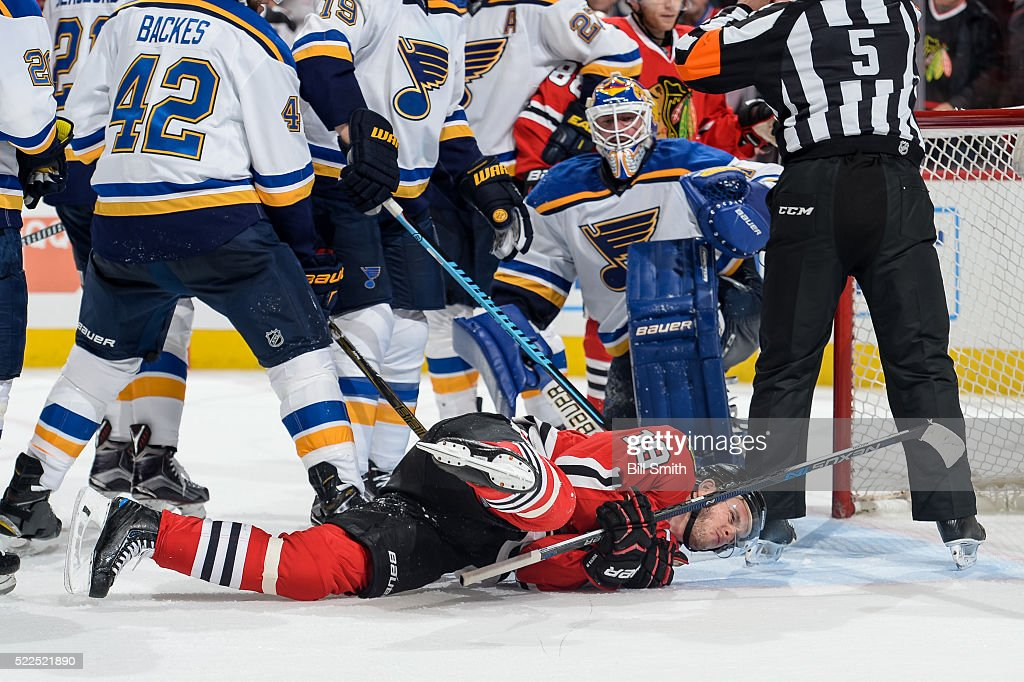 Jonathan Toews #19 of the Chicago Blackhawks lays on the ice after taking a hit in front of goalie Brian Elliott #1 of the St. Louis Blues in the third period of Game Four of the Western Conference First Round during the 2016 NHL Stanley Cup Playoffs at the United Center on April 19, 2016 in Chicago, Illinois.