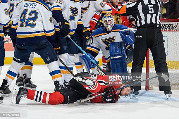 Jonathan Toews of the Chicago Blackhawks lays on the ice after taking a hit in front of goalie Brian Elliott of the St Louis Blues in the third...