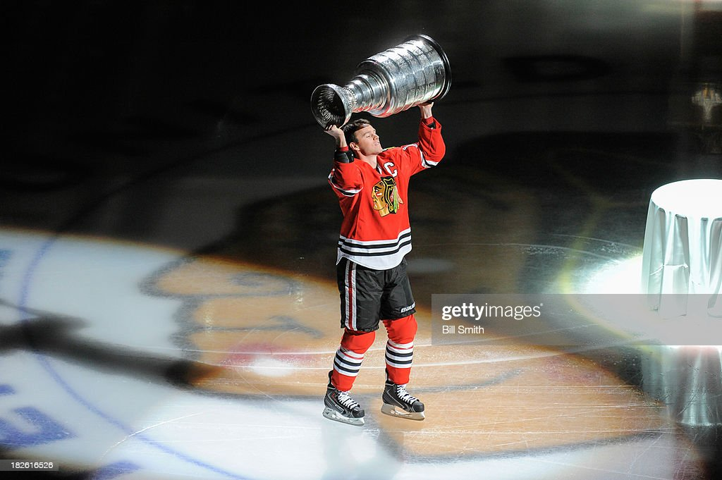 Jonathan Toews #19 of the Chicago Blackhawks lifts up the Stanley Cup during the opening ceremony before the home opener against the Washington Capitals on October 1, 2013 at the United Center in Chicago, Illinois.