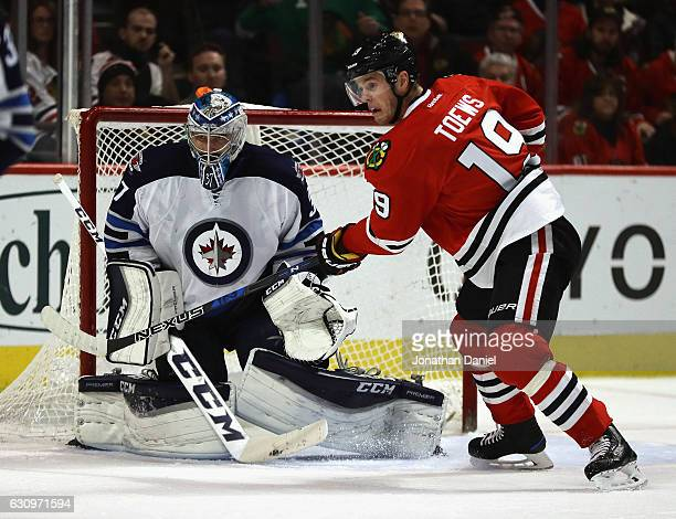 Jonathan Toews of the Chicago Blackhawks looks for a pass in front of Connor Hellebuyck of the Winnipeg Jets at the United Center on December 27 2016...