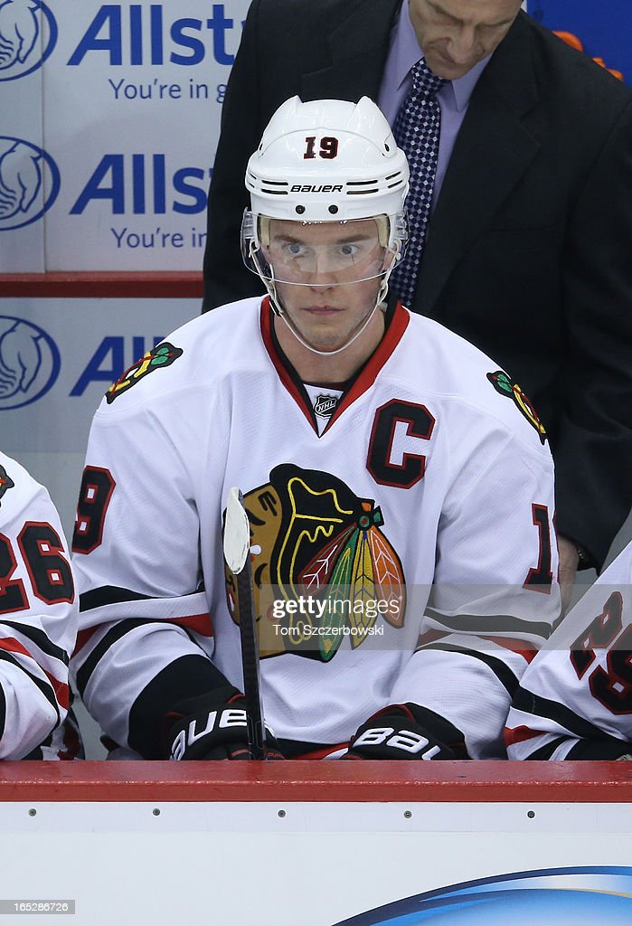 Jonathan Toews #19 of the Chicago Blackhawks looks on from the bench during an NHL game against the Detroit Red Wings at Joe Louis Arena on March 31, 2013 in Detroit, Michigan.
