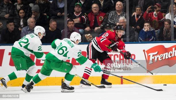 Jonathan Toews of the Chicago Blackhawks passes under pressure from Nikita Zaitsev and Nikita Soshnikov of the Toronto Maple Leafs during the first...