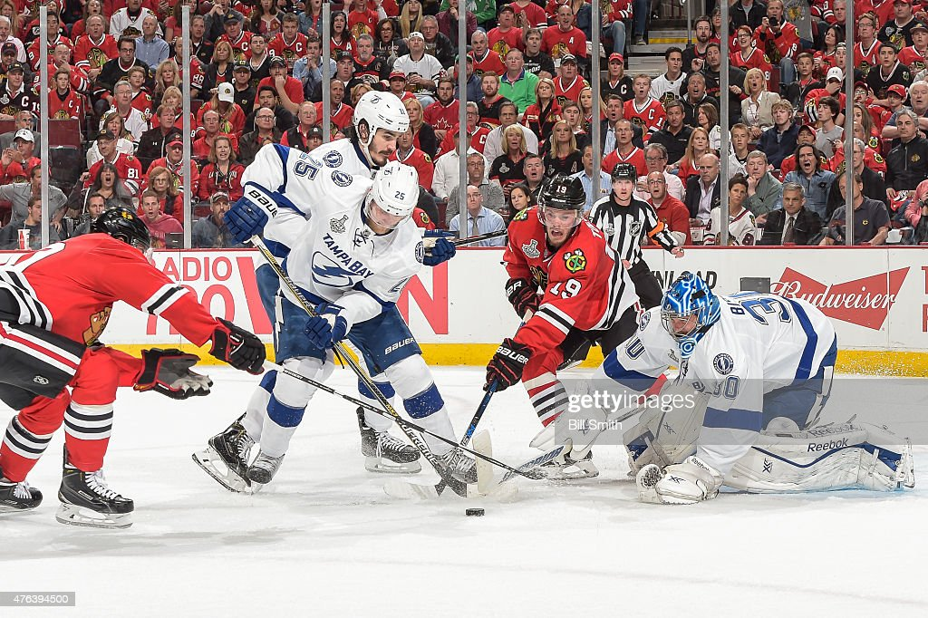 Jonathan Toews #19 of the Chicago Blackhawks reaches for the puck against Matt Carle #25 and Brian Boyle #11 of the Tampa Bay Lightning, as goalie Ben Bishop #30 guards the net, during Game Three of the 2015 NHL Stanley Cup Final at the United Center on June 8, 2015 in Chicago, Illinois.