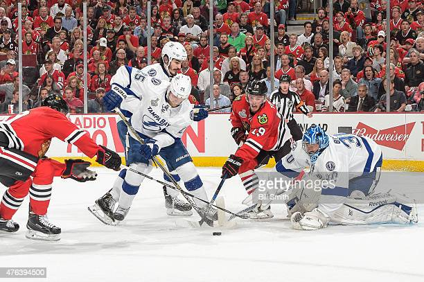 Jonathan Toews of the Chicago Blackhawks reaches for the puck against Matt Carle and Brian Boyle of the Tampa Bay Lightning as goalie Ben Bishop...