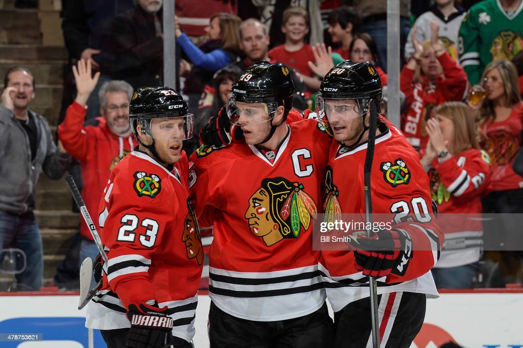 <a gi-track='captionPersonalityLinkClicked' href=/galleries/search?phrase=Jonathan+Toews&family=editorial&specificpeople=537799 ng-click='$event.stopPropagation()'>Jonathan Toews</a> #19 of the Chicago Blackhawks (middle) reacts with teammates <a gi-track='captionPersonalityLinkClicked' href=/galleries/search?phrase=Kris+Versteeg&family=editorial&specificpeople=2242969 ng-click='$event.stopPropagation()'>Kris Versteeg</a> #23 and <a gi-track='captionPersonalityLinkClicked' href=/galleries/search?phrase=Brandon+Saad&family=editorial&specificpeople=7128385 ng-click='$event.stopPropagation()'>Brandon Saad</a> #20 after scoring against the Nashville Predators in the first period during the NHL game on March 14, 2014 at the United Center in Chicago, Illinois.