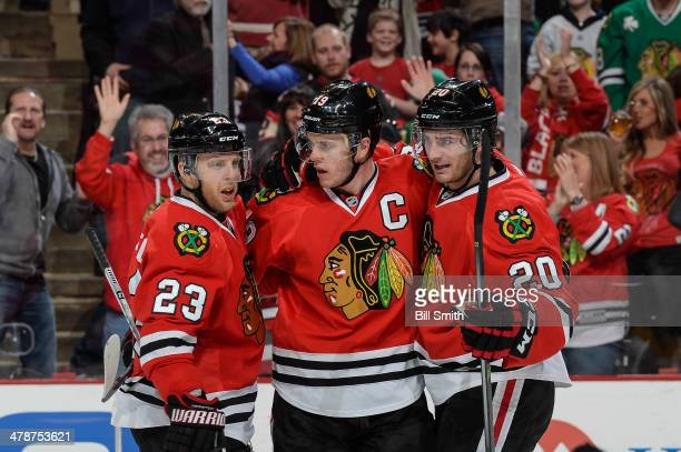 Jonathan Toews of the Chicago Blackhawks reacts with teammates Kris Versteeg and Brandon Saad after scoring against the Nashville Predators in the...