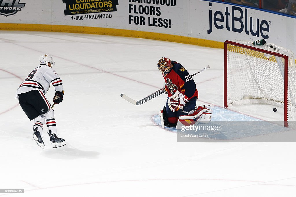 <a gi-track='captionPersonalityLinkClicked' href=/galleries/search?phrase=Jonathan+Toews&family=editorial&specificpeople=537799 ng-click='$event.stopPropagation()'>Jonathan Toews</a> #19 of the Chicago Blackhawks scores a shoot-out goal past goaltender <a gi-track='captionPersonalityLinkClicked' href=/galleries/search?phrase=Jacob+Markstrom&family=editorial&specificpeople=5370948 ng-click='$event.stopPropagation()'>Jacob Markstrom</a> #25 of the Florida Panthers at the BB&T Center on October 22, 2013 in Sunrise, Florida. The Blackhawks defeated the Panthers 3-2 in a shoot-out.