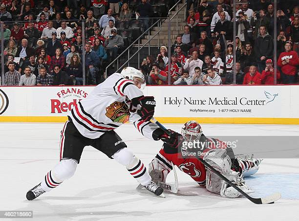 Jonathan Toews of the Chicago Blackhawks scores the game winning goal in the shootout against Keith Kincaid of the New Jersey Devils at the...