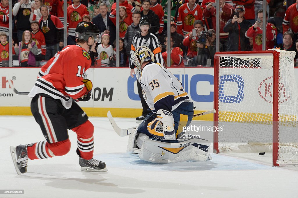 Jonathan Toews #19 of the Chicago Blackhawks scores the game winning goal on goalie Pekka Rinne #35 of the Nashville Predators in overtime of the NHL game at the United Center on December 29, 2014 in Chicago, Illinois.