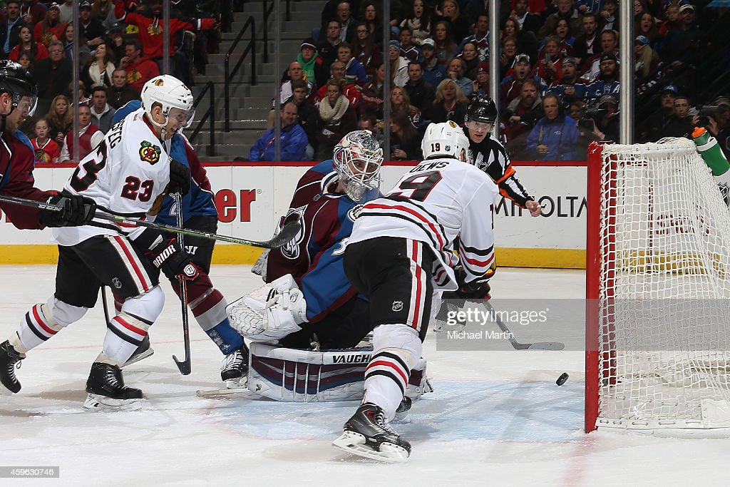 <a gi-track='captionPersonalityLinkClicked' href=/galleries/search?phrase=Jonathan+Toews&family=editorial&specificpeople=537799 ng-click='$event.stopPropagation()'>Jonathan Toews</a> #19 of the Chicago Blackhawks scores while teammate <a gi-track='captionPersonalityLinkClicked' href=/galleries/search?phrase=Kris+Versteeg&family=editorial&specificpeople=2242969 ng-click='$event.stopPropagation()'>Kris Versteeg</a> #23 looks on against goaltender <a gi-track='captionPersonalityLinkClicked' href=/galleries/search?phrase=Calvin+Pickard&family=editorial&specificpeople=6698843 ng-click='$event.stopPropagation()'>Calvin Pickard</a> #31 the Colorado Avalanche at the Pepsi Center on November 26, 2014 in Denver, Colorado.