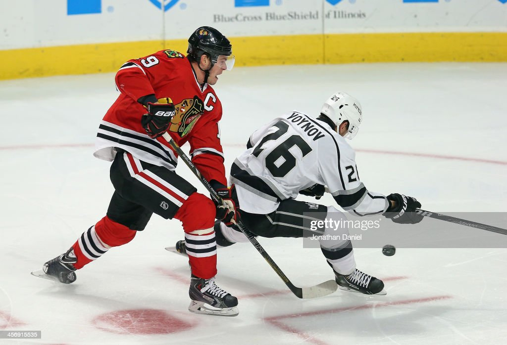 Jonathan Toews of the Chicago Blackhawks shoots the puck between the legs of Slava Voynov of the Los Angeles Kings at the United Center on December...