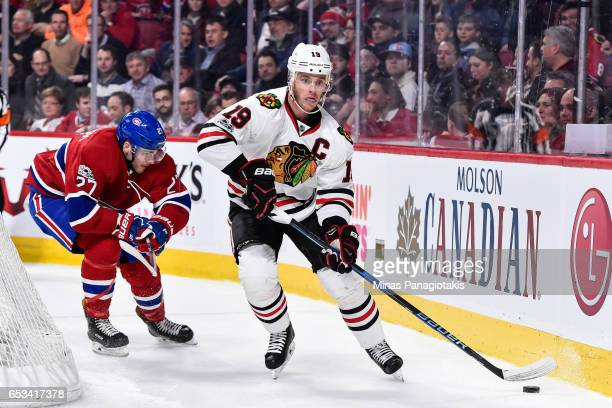 Jonathan Toews of the Chicago Blackhawks skates the puck against Alex Galchenyuk of the Montreal Canadiens during the NHL game at the Bell Centre on...
